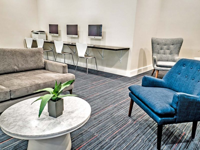 This picture unveils a beautiful setup of a clubhouse business center with a relaxing sofa.